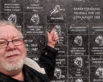 Barrie Stradling pointing at the Wall of Dedications at Millwall.