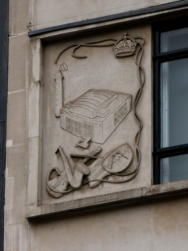 One of three plaques celebrating the 1951 Festival of Britain on the side of Zara just east of Oxford Circus. This one depicts the Royal Festival Hall, which had just been built.
